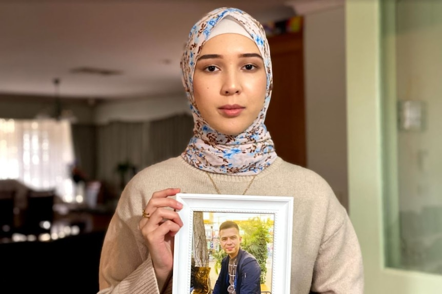 A woman holds up a photo of a man.