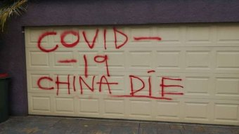 """A garage door spray painted with the words Covid-19 China die""""."""