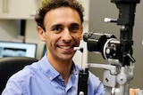 A smiling Kristopher Rallah-Baker sits in front of eye testing equipment.