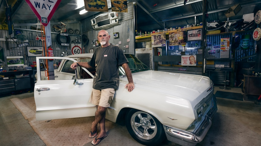 A man leans against a vintage car in a garage filled with automobile tools and paraphernalia.