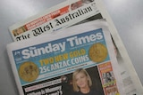 Copies of The Sunday Times and The West Australian lie on a grey table.
