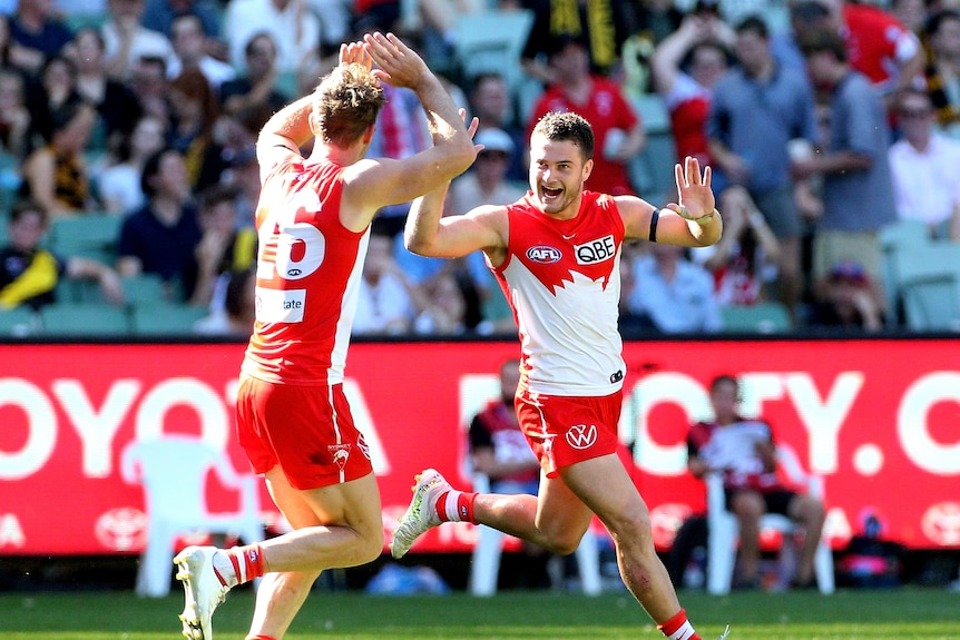 An AFL footballer grins and runs toward his teammate in celebration.