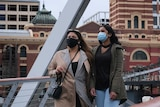 Two women wearing face masks and earthy coloured coats in Melbourne.