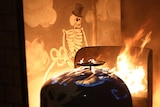Re-enactment of carriage on fire with skeleton painting in background.