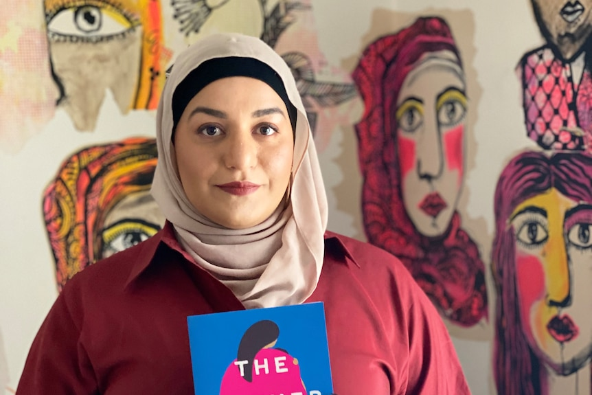 Author Amani Haydar is wearing a blush coloured hijab and holding a copy of her book The Mother Wound