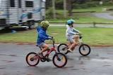 Two boys riding bikes in a caravan park