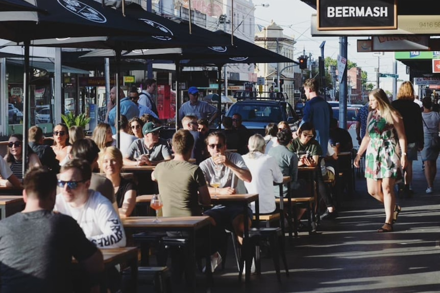 Photo of dozens of people sitting out the front of a busy bar
