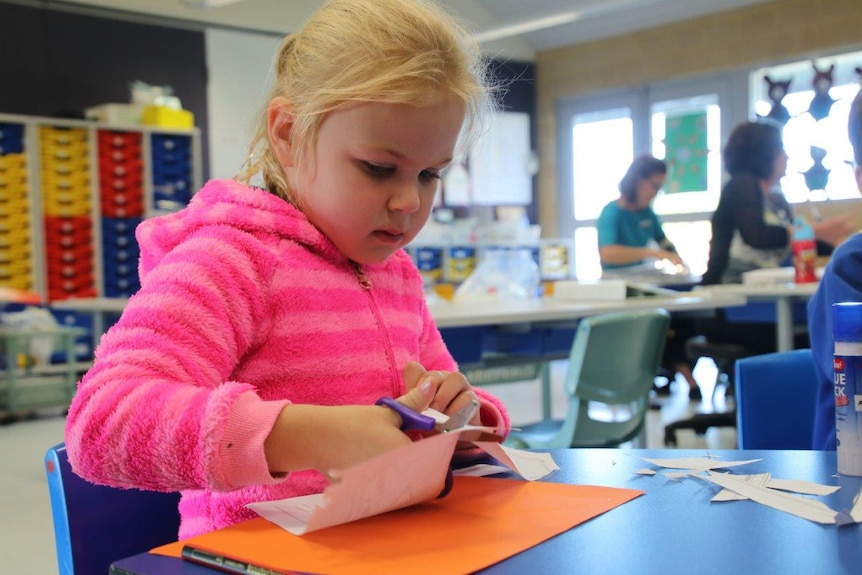 A young girl wearing a pink jumper with blonde hair sits at a table in a classroom cutting paper with scissors.