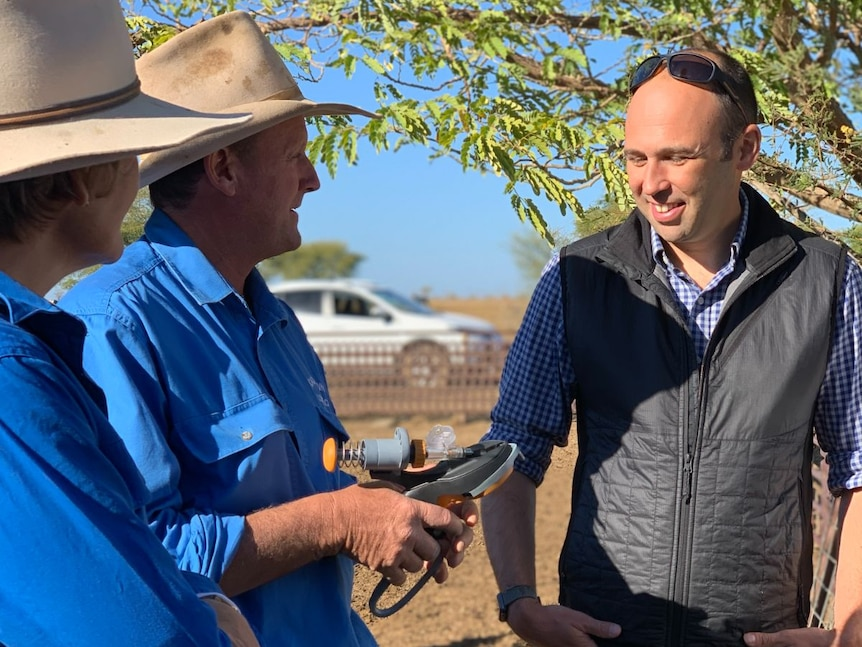 Two farmers in blue shirts and hats hold a device. A man in a puffer vest stands beside them.