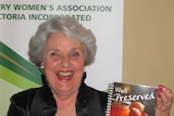 Carol Clay at a Country Women's Assocation event holding up a cook book