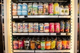 A bottle shop fridge full of brightly coloured craft beer cans