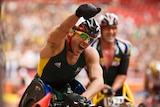 Kurt Fearnley raises his fist in celebration after a wheelchair race competing for Australia