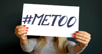 A woman holding a sign in front of her face that says #METOO.