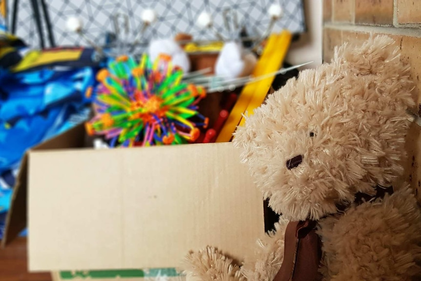 A teddy bear and a box of toys in a children's room.