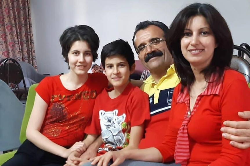 A photo of a family of four, wearing red shirts sitting next to each other.