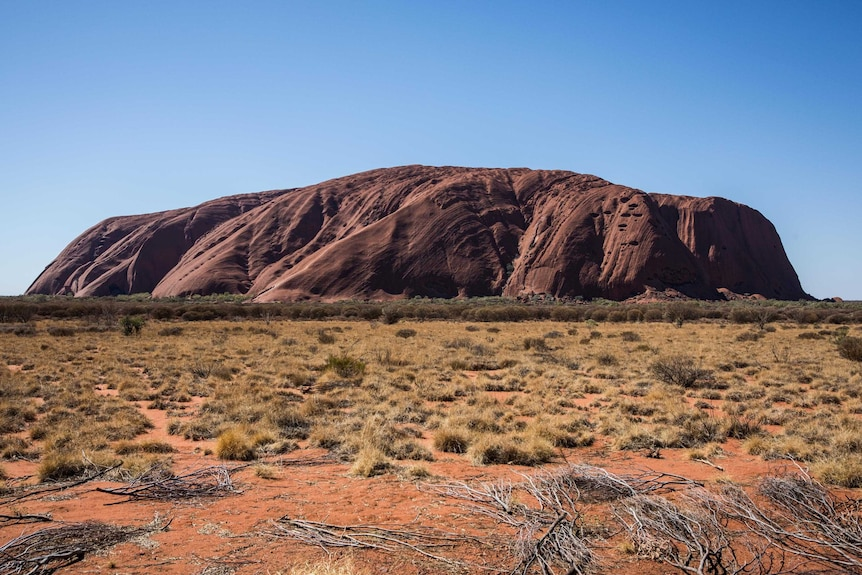 An image of Uluru, rock formation with the sun hitting its flank.