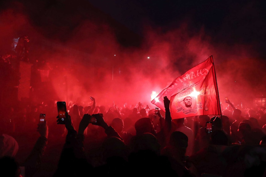 Football fans are bathed in the red light of flares as they celebrate outside their home ground.