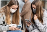 Two teenage girls on their phones sitting close together while wearing masks