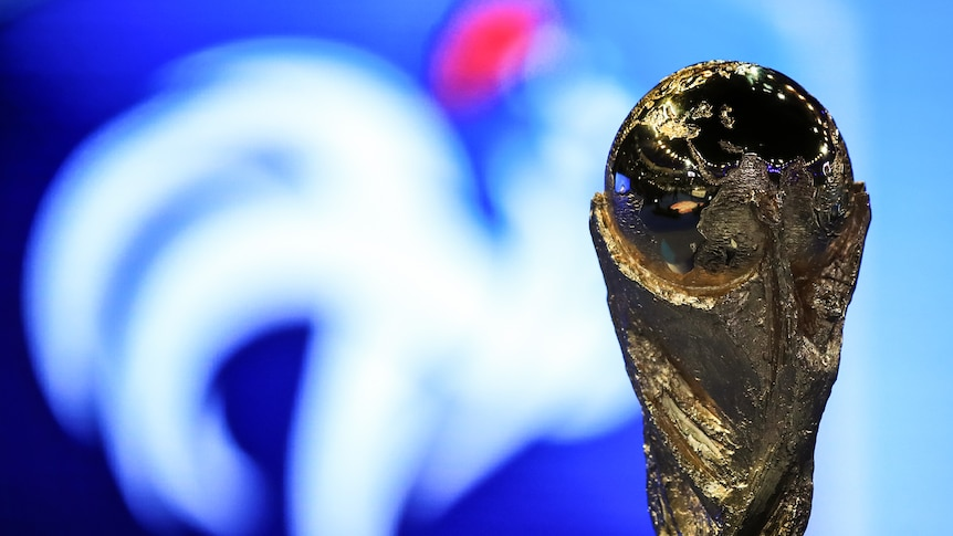 The World Cup trophy in front of a blue and white background