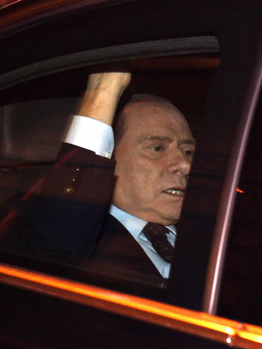 End of an era: Silvio Berlusconi leaves parliament after the vote.
