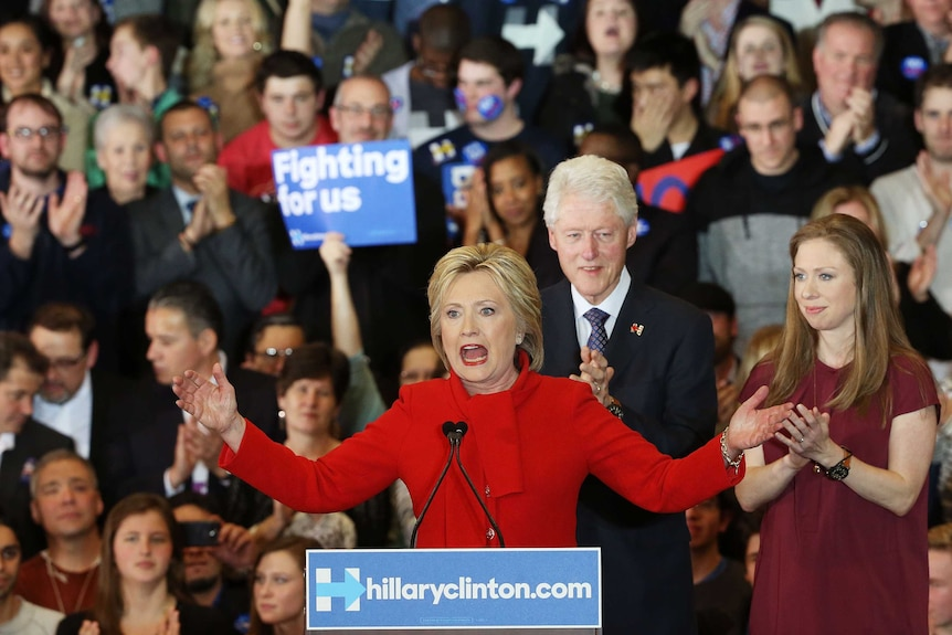 Hillary Clinton on stage, addressing supporters, as Bill Clinton and daughter Chelsea Clinton look on.