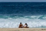 A couple sunbake while sitting on the beach, against a backdrop of blue ocean.