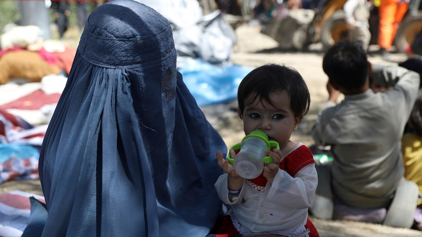 Woman wearing a blue burqa holds a young child drinking from a bottle.