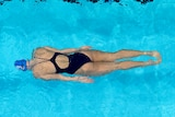 """A swimmer is underwater, seen from above, warming up at the Australian Olympic trials under a sign reading """"It's Tokyo time""""."""
