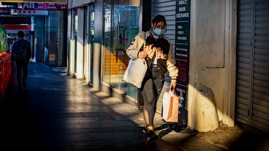 a woman in a mask shopping on a sydney street