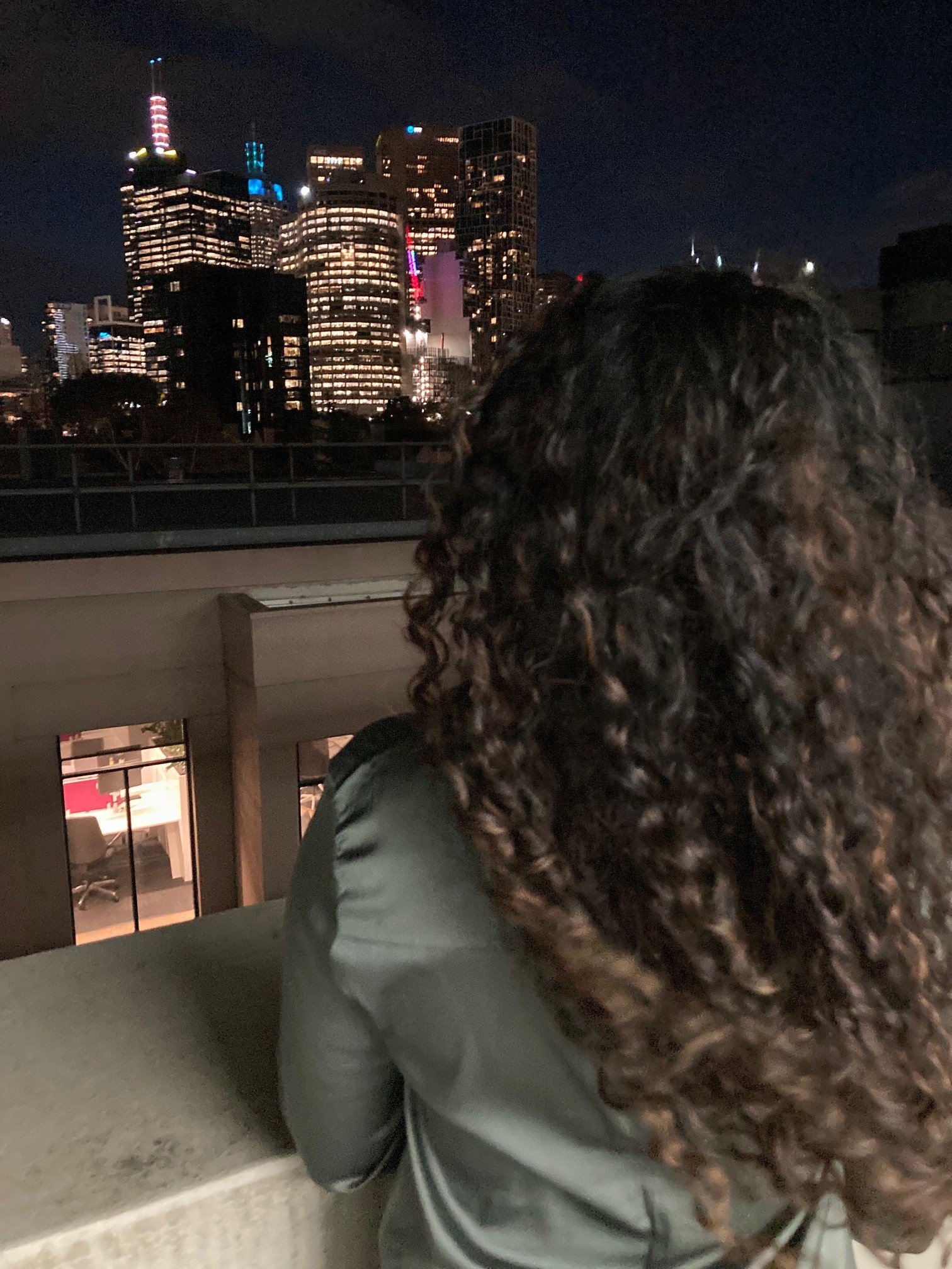 The back of a woman's head as she looks at the skyline of the city at night.