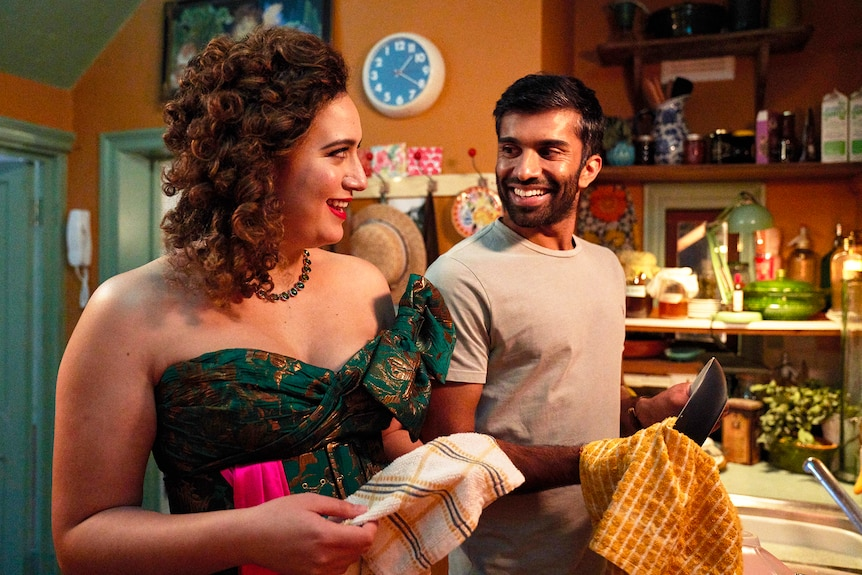 Rose Matafeo in a lavish gown dries the dishes in her cluttered kitchen with Nikesh Patel in Starstruck