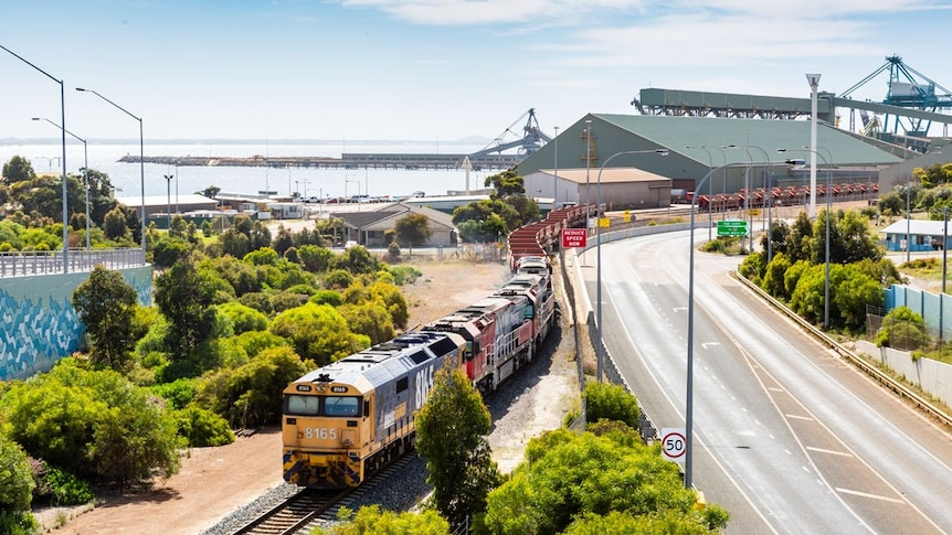 A landscape showing the Esperance port, ocean and a train full of iron ore rolling past