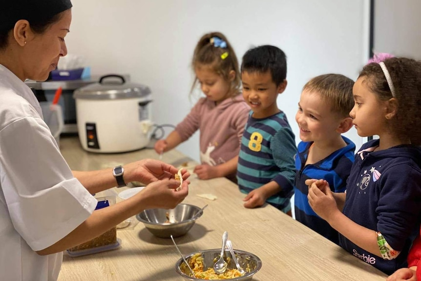 Four children watch on as an adult shows them how she is preparing some food.