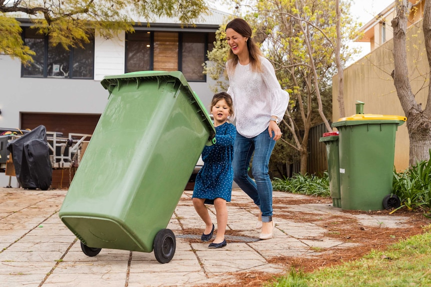 A small girl in a blue dress and a woman wearing jeans push a green bin on a driveway.