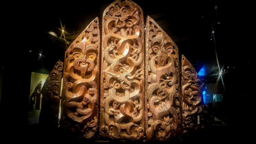 Five intricately carved wooden panels spotlit in a dark room.