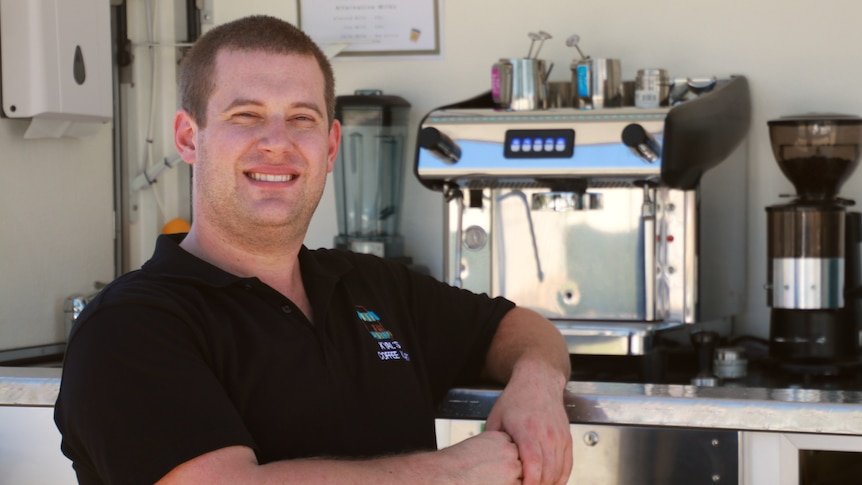 A short haired man wearing a black polo stands in front of a coffee machine