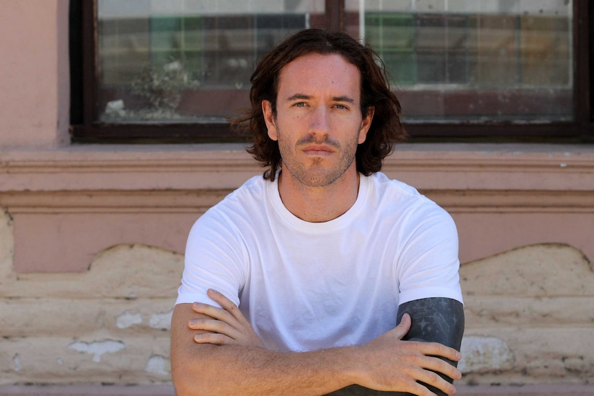 Man in white t-shirt with arms crossed looking at the camera.