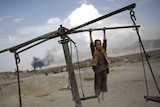 An Afghan boy hangs from a merry-go-round on a hill top in Kabul, Afghanistan