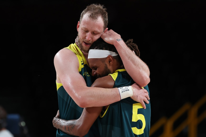 Joe Ingles hugs Patty Mills after Australia won the bronze-medal basketball game against Slovenia at the Tokyo Olympics.