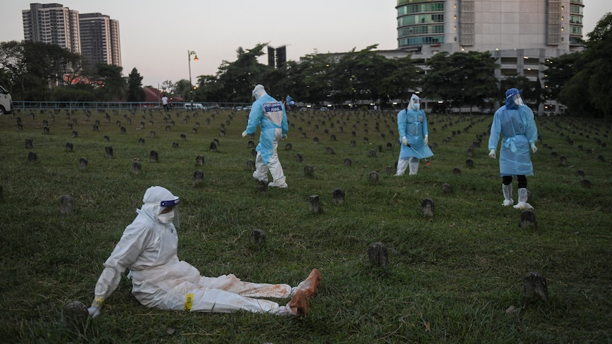 Health workers in PPE take a break while burying bodies of COVID-19 victims