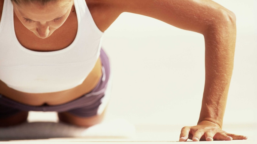 A woman doing a push-up on the ground.