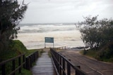 Rough seas from cyclone Hamish pound Happy Valley boardwalk on Fraser Island.