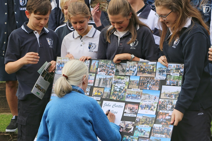 Four school children show a photo board to Dr Jane Goodall, who signs it for them.