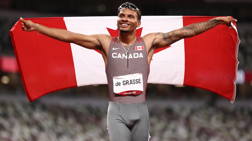 A male sprinter holds the Canadian flag behind his back after winning gold at the Tokyo Olympics.