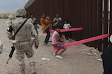 Armed guards walk past children and adults playing on bright pink seesaws which stretch through the steel slats of the wall