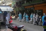 People in full PPE stand in a street while a man sitting in a plastic chair gets tested for coronavirus.
