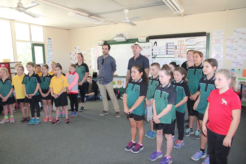 A classroom full of small kids with two adults standing in the middle singing