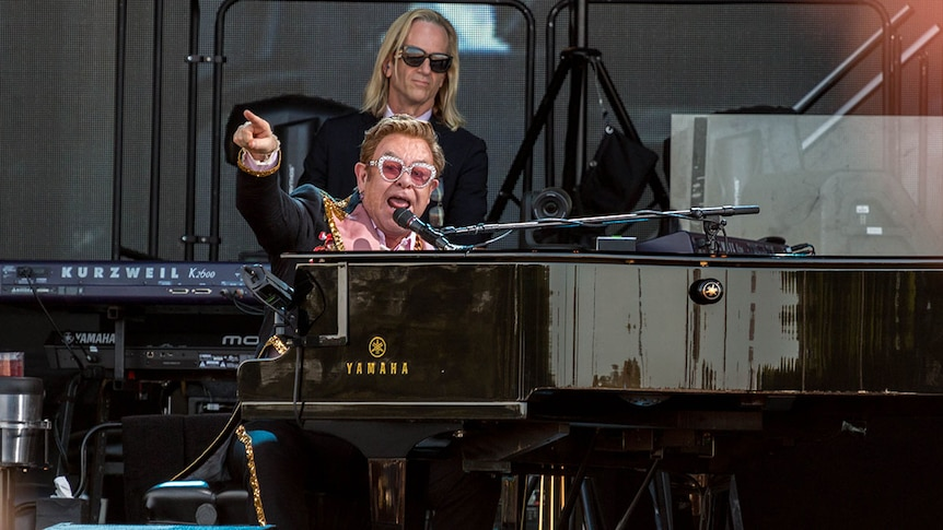 Performer Sir Elton John sits at his piano on a stage and points to the crowd.
