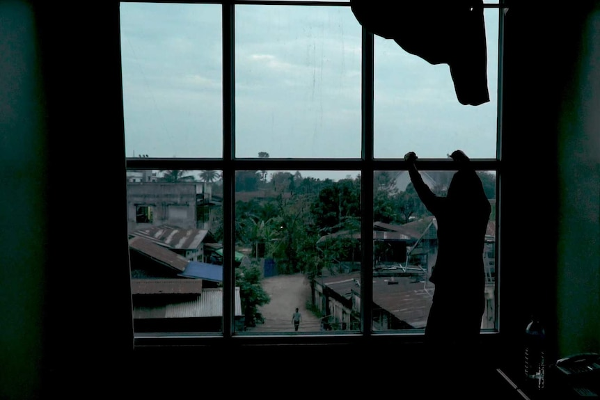A victim of human trafficking from Myanmar's Kachin state stares out a window into a dirt street with rusted roofs.