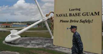 A US soldier walks past a sign for the Naval Base Guam.